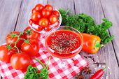 Tomato juice in goblet and fresh vegetables on napkin on wooden background