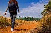 Young Woman With Backpack Walking On A Dusty Country Road