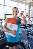 sport, fitness, slimming and people concept - smiling woman with scales and towel showing thumbs up in gym