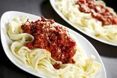 Spaghetti bolognese with parmesan cheese in two plates on black table