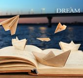 Origami boats on old book on bridge background
