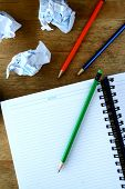 Notebook, crumpled papers and colorful pencils