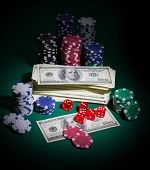 Stack of dollars dices and chips on green table