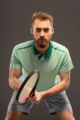 Handsome young man in polo shirt holding tennis racket