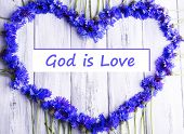 Beautiful cornflowers and text God is Love on wooden background