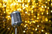 Silver retro microphone on golden festive background, Karaoke party concept
