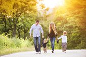 stock photo of children walking  - Happy young family walking down the road outside in green nature - JPG