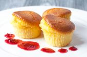 Delicious Muffins On A White Plate. With A Red Berry Sauce. Gray Background. (soft Focus)