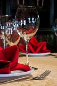 Table In A Restaurant With A Tablecloth, Red Napkins, Wine Glasses And Cutlery.