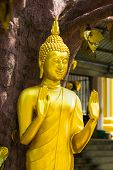 Buddha Statue In Tiger Temple With Golden Leaves, Krabi, Thailand