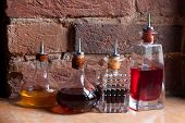Medical Jars With Colorful Potions On Brick Wall Background. Medicine Bottle. Old Pharmacy Bottles.