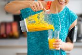 Close-up On Fitness Young Woman Pouring Pumpkin Smoothie In Glass
