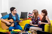 Man playing a guitar with girlfriends