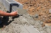 bricklayer builds a wall, construction of concrete  walls