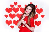 White caucasian woman with red lips holding a champagne glass on heart shaped background.Valentine`s