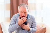 Old man coughing and holding breast having a bad cold