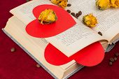 Several Roses And Two Hearts Lying On The Book With Coffee Beans