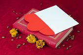 Two Hearts In The Envelope Lying On The Book With Roses