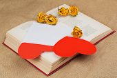 Two Hearts In The Envelope With Dried Roses Lying On The Book