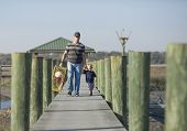 father or grandfather and son or grandson walking down dock with crab trap