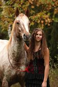foto of appaloosa  - Amazing girl standing next to the appaloosa horse in autumn