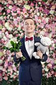 Young Funny Groom With Bouquette And Toy On The Flowers Wall Background.