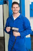 Smiling mechanic holding power drill at the repair garage