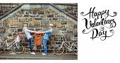 Hip young couple dancing by brick wall with their bikes against happy valentines day