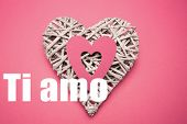 Wicker heart ornament with paper cut out against ti amo