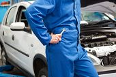 Male mechanic with spanner leaning on car