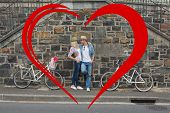 Hip young couple standing by brick wall with their bikes against heart