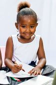 Little African Girl Drawing With Crayons.