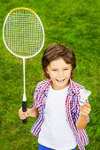 foto of shuttlecock  - Top view of happy little boy holding badminton racket and shuttlecock while standing on green grass