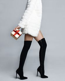 stock photo of stocking-foot  - Slender female in elegant boots stockings with gift - JPG