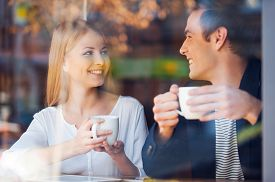 stock photo of hot couple  - Through a glass shot of beautiful young couple looking at each other and smiling while enjoying coffee in cafe together - JPG