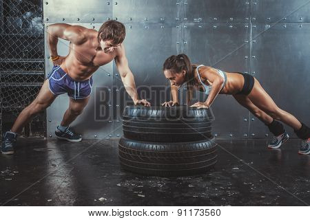 poster of Sportswomen. Fit sporty woman and man doing push ups on tire strength power training concept crossfi