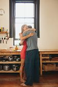 stock photo of morning  - Indoor shot of young couple embracing each other in kitchen - JPG