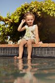 stock photo of wet feet  - Outdoor shot of a little girl dipping her feet in the pool - JPG