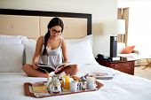 picture of bed breakfast  - Attractive woman relaxing in bed with a breakfast tray and reading a book - JPG
