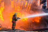 stock photo of fire extinguishers  - Fireman extinguishes a fire in an old wooden house - JPG