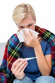 foto of blowing nose  - Sick blonde woman blowing her nose and checking the thermometer on white background - JPG