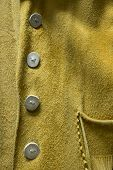 image of wrangler  - A close up photo of an antique buckskin leather coat with unique elk horn buttons - JPG