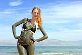 picture of israel people  - Young woman enjoying natural mineral mud sourced from Dead sea - JPG