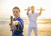 picture of martial arts girl  - Two martial arts athletes training with weapons on the beach at sunrise  - JPG