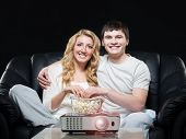 stock photo of watching movie  - Young family watching a movie or a sport broadcast on a laser projector sitting on a sofa  - JPG