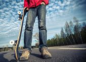 stock photo of skate board  - Rider standing on the asphalt road and holding skate board over the blue sky background - JPG