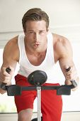 picture of exercise bike  - Young Man On Exercise Bike - JPG