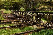 pic of old bridge  - Old rusty abandoned steel bridge over the river - JPG