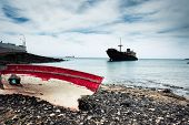 picture of old boat  - boat on the backgrond with old broken agrounded ship  - JPG