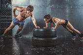 Sportswomen. Fit sporty woman and man doing push ups on tire strength power training concept crossfi poster